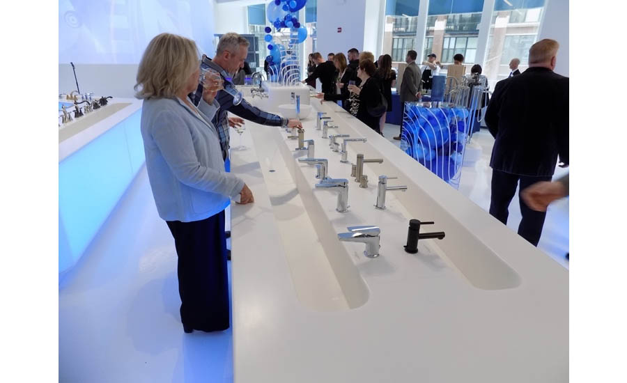 Guests at the grand opening event try out some more of Moen