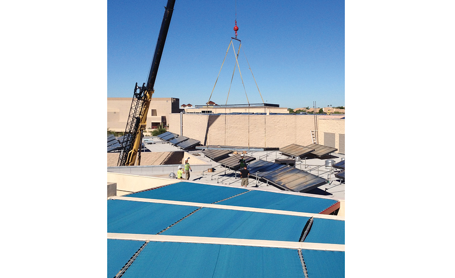 Workers lower panels into place on topof Desert Mountain High School in Scottsdale, Arizona