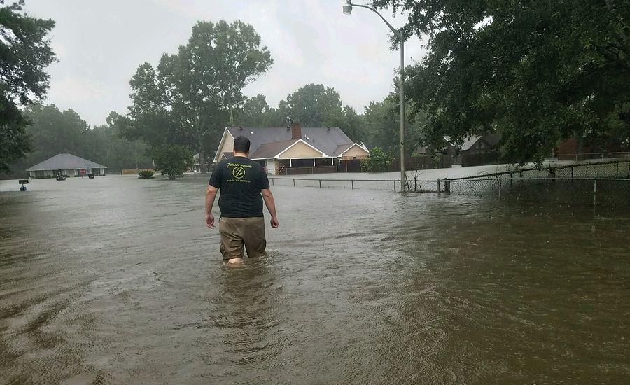 Jason Horcasitas, A.H. Deveney's inside sales manager, wades through flood waters near his home, which was damaged severely