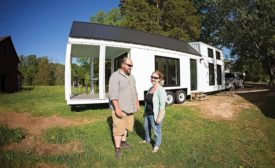 Tiny-home builders Johanna and Tom Elsner stand in front of one of their homes